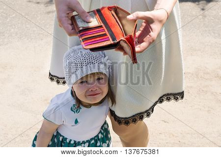 crying little girl and empty wallet outdoors