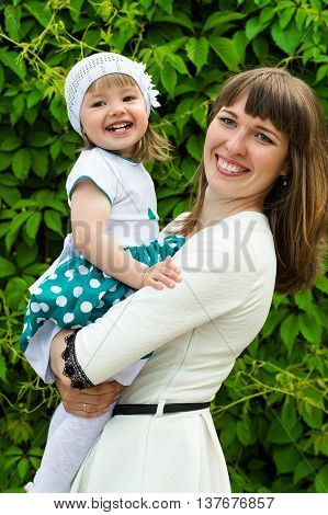 happy mother with a daughter on hands smiling