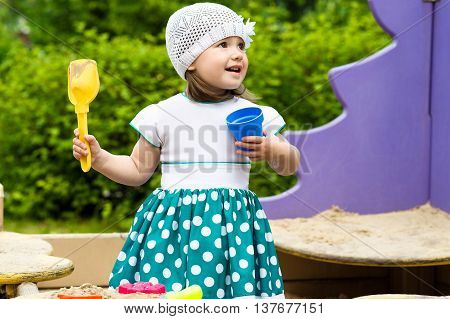 little girl playing in the sandbox outdoors