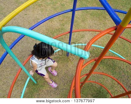 Lonely Girl sit on Clamber player in playground