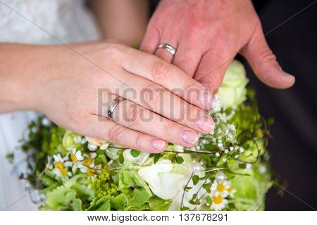 bride's and grooms hand with rings on flowers