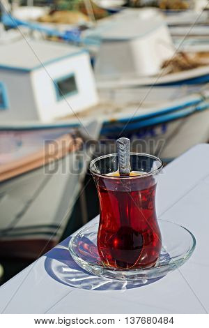 A glass of Turkish tea by the harbor