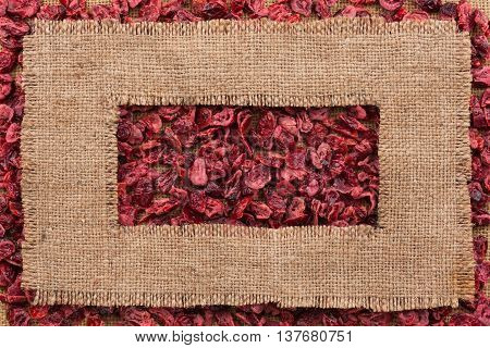 Frame made of rough burlap lies on dried cranberry as background