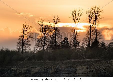 Sunset over the forest and the steep cliff of the quarry