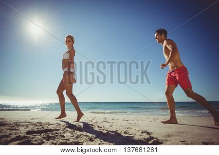 Young couple running on beach on a sunny day