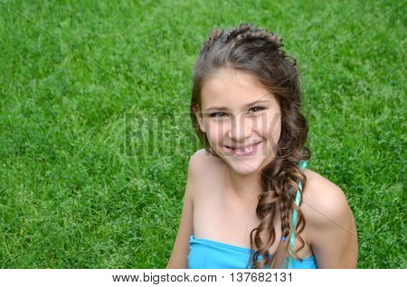 Hairstyle with long hair, a fine weave - a young girl on a background of green grass