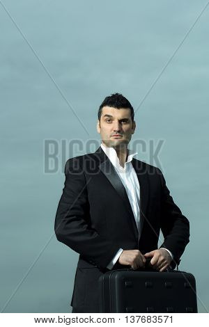 handsome male businessman with surprised face in black formal jacket and white shirt with brief case on leather office arm chair outdoor on cloudy sky background