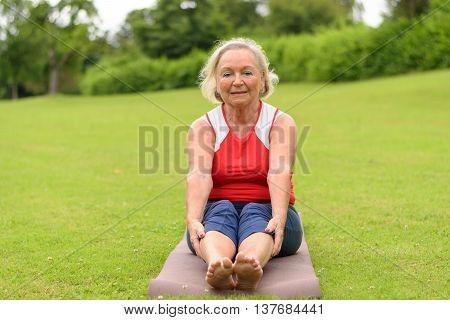 Senior Woman Sitting On Yoga Mat