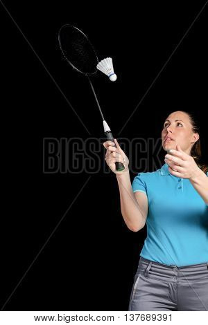 Athlete playing badminton on black background