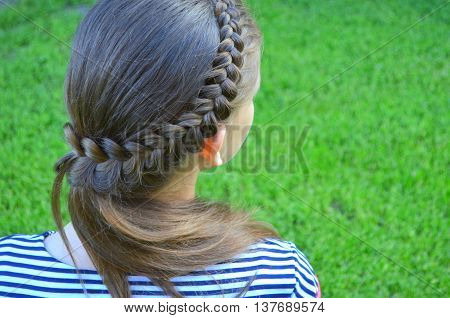 Hairstyle with long hair a young girl on a background of green grass