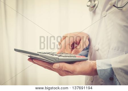 closeup of a young asian healthcare professional wearing a white coat calculates on an electronic calculator
