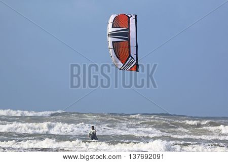 Kitesurfer riding in waves on the sea
