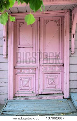 Pink wooden stylish retro cracked door with chipping paint at the entrance of old building on the street. The background and texture of the door was weathered and became old-fashioned.