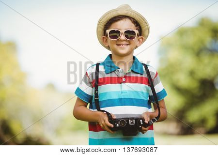 Smiling young boy in sunglasses holding a camera in park