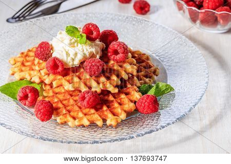 Waffles garnished with mascarpone and raspberries selective focus.