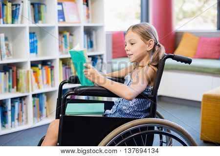 Disabled school girl reading book in library at school