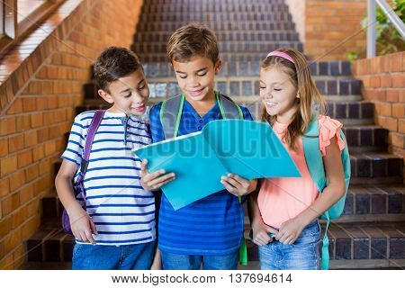 Smiling school kids reading a book on staircase at school