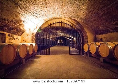 Winery cellar with special edition wine waiting in barrels for a few years until it is ready at Chateau la Nerthe.
