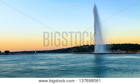 A view of Geneva's landmark as seen from Jardim Anlgais during a blue sky day. The Jet d'Eau is a large fountain in Geneva Switzerland and is one of the city's most famous landmarks being featured on the city's official tourism web site and on the officia