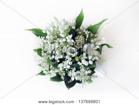 Wedding bouquet of lilies of the valley on a white background