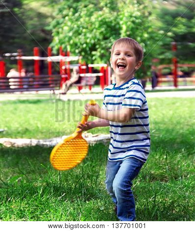 Little Boy Playing Tennis Happy Cheerful Boy Holding A Racket Standing On The Green Grass,