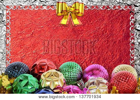 Christmas background with christmas ball and pattern on the red foil background
