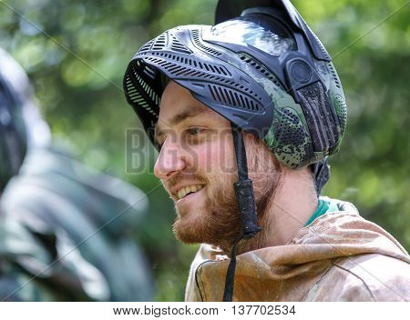 Smiling handsome young man in opened paintball mask