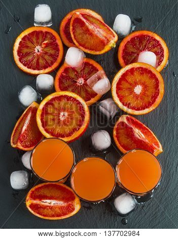 Sliced Sicilian red oranges and orange juice in small glasses on black stone background. Top view.
