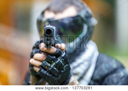 Cool shooter with handgun in paintball helmet aiming in camera. Focus on top of the gun.