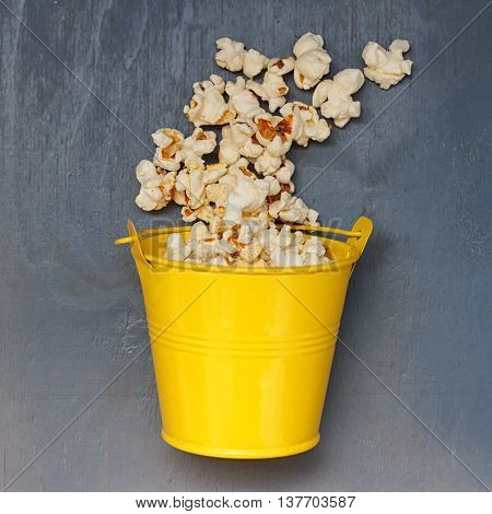 popcorn chaotic jumps out of the yellow metal bucket on a blue background
