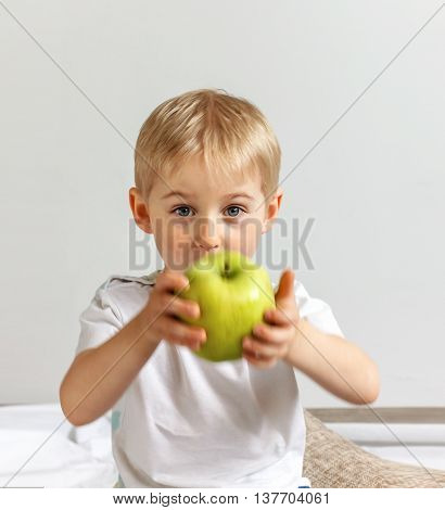 Happy Cheerful Boy Eats The Big Apple, The Child Is The Fruit Green
