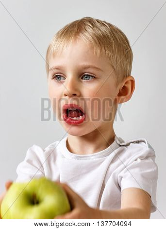 The Little Boy Does Not Want To Eat An Apple, Eating Apple Green, Giving No Appetite On A White Back