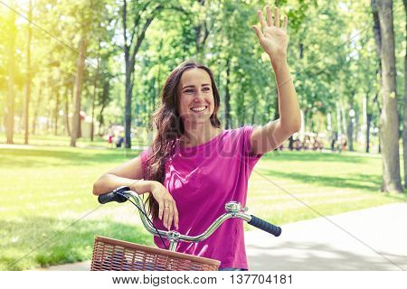 Young pretty woman made a stop during her bicycle ride in the park to wave and greet somebody
