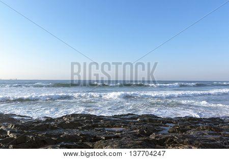 Dark rocks ocean waves and blue skyline seascape on beach in South Africa