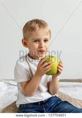 Happy cheerful boy eats the big apple the child is the fruit green soft focus