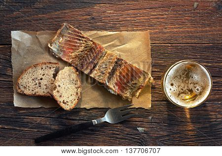 Fish on a paper bread and glass of beer on old wooden table top view