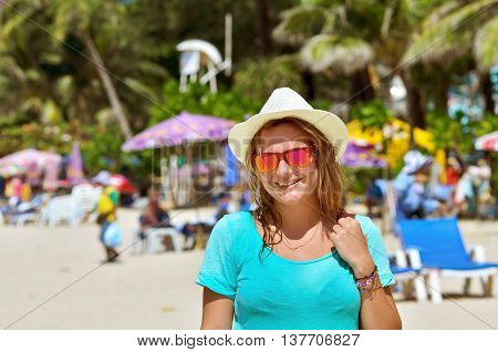 Portrait of beautiful young woman at the beach. girl in a hat.