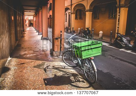 Bologna Italy April 25 2016: parked bicycle on narrow street along an empty portico