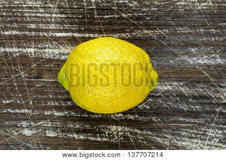 Fresh yellow lemon on the wooden background