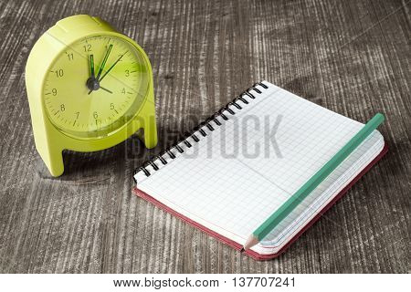 Time management concept: green alarm clock pencil and notebook