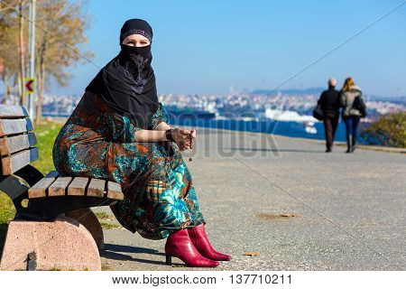 Muslim Style dressed Lady sitting on wooden Bench on Seafront Promenade of Istanbul City