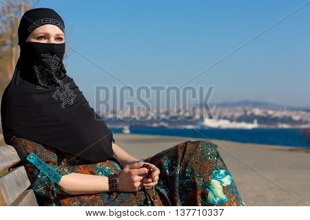 Muslim Style dressed Lady sitting on wooden Bench on Seafront Promenade of Istanbul City Pensive look holding Rosary