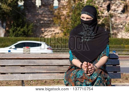 Muslim Style dressed Lady sitting on wooden Bench Seafront Promenade of Istanbul City Pensive sad look holding Rosary Ancient Wall and Urban Landscape on Background
