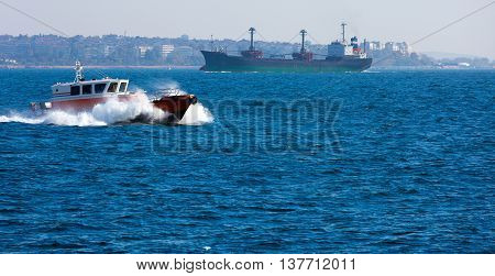 Small and big Ships moving throw Bosporus Channel conquering stormy Sea Waves