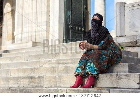 Muslim Style dressed Lady sitting on Marble Steps of Blue Mosque of Istanbul City Pensive look holding Rosary