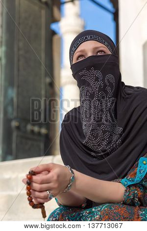 Portrait of Arabic Lady sitting Marble Steps of Blue Mosque holding Rosary and Looking Up