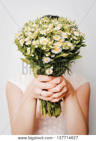Girl with bouquet of camomile at white wall