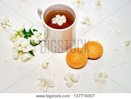 Tea Cup With Fragrant Jasmine Flowers And Cookies On Background