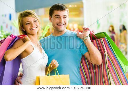 Homem feliz com paperbags na mão tocando sua namorada enquanto o shopping