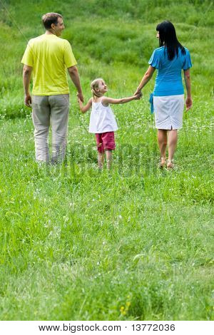 Portrait of family walking down green meadow at leisure in summer